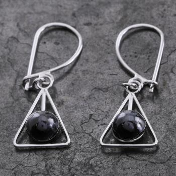 handmade earrings with cabochon cut sapphire dangling on a hook