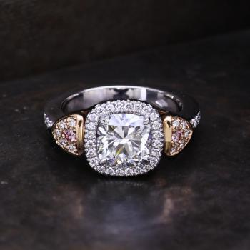 Entouragering with a central cushion cut diamond surrounded by smaller white and two fancy pink brillant cut diamonds.