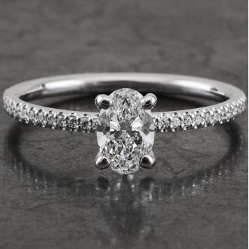 ring with an oval cut diamond set with four rounded claws on a round profiled band castle pavé set with small brilliant cut diamonds