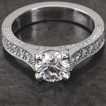 engagement ring with a brilliant cut diamond set in four crossed prongs on a band at the top and set with brilliant cut diamonds finished with millegrain