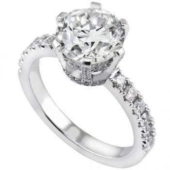 handmade solitaire ring with a central brilliant cut diamond in six castle set square prongs against two integrated double roundels on a sideband also set with smaller brilliants