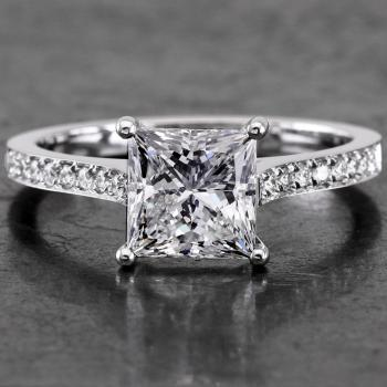 solitaire ring with a princess cut diamond slightly lower set into four roundned prongs on a band with palmets set with smaller brilliant cut diamonds