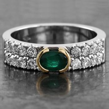 ring with an oval cut emerald set in an open bezel setting and flanked by castle set brilliant cut diamonds