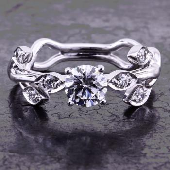 handmade soltaire ring with a brilliant cut diamond along which small leaves decorated with diamonds