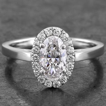 entourage ring with a central oval cut diamond surrounded with smaller brilliants on an unset band with palmettes (V slightly higher mounted)