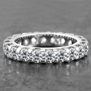 alliance ring with brilliant cut diamonds set with two flat prongs in between the precious stones