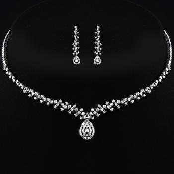 set of necklace, bracelet and earrings with diamonds zigzag next to each other set with prongs and with a pear-shaped pendant with two central brilliant cut diamonds surrounded by two rows of castle set smaller brilliant cut diamonds