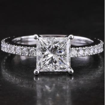 solitaire ring with a central princess cut diamond in a slightly more straight wire settng flanked by castle-set brilliant-cut diamonds on the slim band