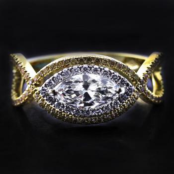 halo ring with a central marquise cut diamond between a braided band castle set with fancy brown diamonds and surrounded by smaller brilliant cut diamonds