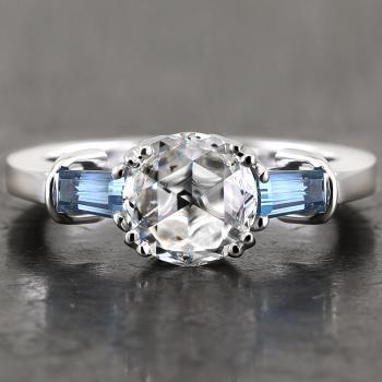 engagement ring with a central rose cut diamond flanked by two tapered cut aquamarines