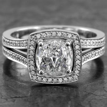 halo set or entourage ring with a central cushion cut diamond surrounded by smaller castle pavé set brilliant cut diamonds finished with filet or engraving on a double slightly wider band (construction without middle band)