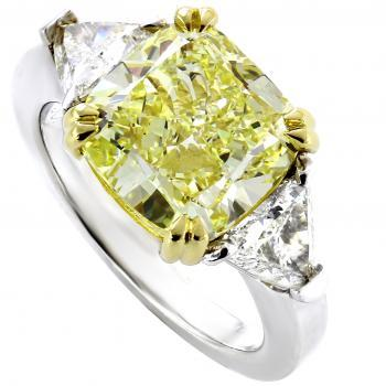Handgemaakte ring met een fancy yellow cushion geslepen diamant met twee triangle of driehoekig geslepen diamanten ernaast