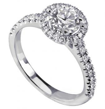halo ring with a larger central brilliant cut diamond and smaller diamonds castle set on the thinner band with palmettes