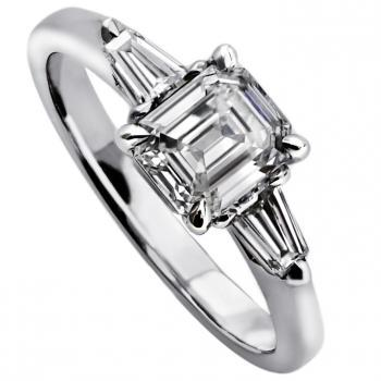 handmade ring with an emerald cut diamond flanked by 2 tapers on a smaller band