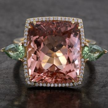 entourage or halo ring with a faceted antique or cushion cut morganite or beryl of approximately 13ct surrounded by small brilliant cut diamonds and flanked by pear-shaped peridots