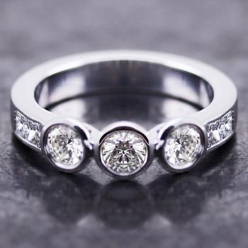 trilogy ring with three brilliant cut diamonds set in a round bezel settings and flanked by two princess cut diamonds on each side
