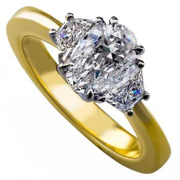 ring with an oval cut diamond diamond and two smaller trapeze shaped diamonds wearable together with a wedding band
