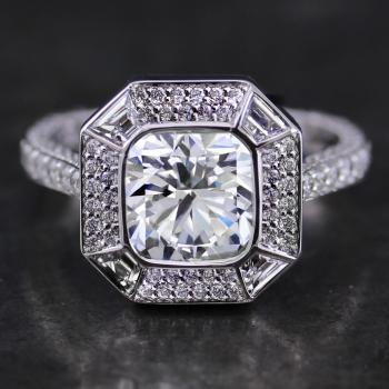 double halo ring with a cushion cut diamond bezel set and surrounded by four trapees cut and pavé set diamonds on a single band pavé set with three rows of smaller diamonds