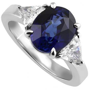 ring with an oval cut sapphire next to which two triangle cut diamonds on a slim band with very slightly rounded profile