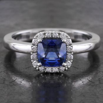 halo ring with a central cushion cut sapphire surrounded with accent stones in castle pavé setting mounted on an open slightly rounded band (compatible with a wedding ring)
