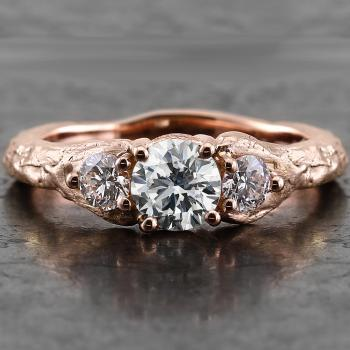 organic looking ring with a larger central brilliant cut diamond flanked by two smaller diamonds