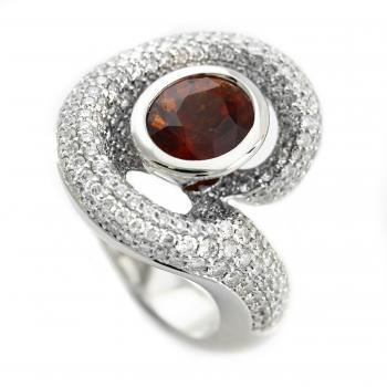 pavé entourage ring with an oval red garnet set in a ring embraced by smaller brilliant cut diamonds