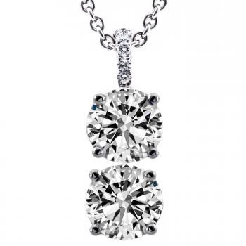 duo pendant with two larger brilliant cut diamonds set with four claws on a bracket castle set with smaller brilliants