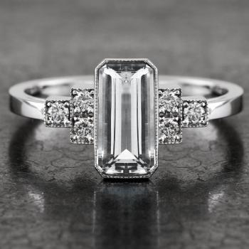 ring with a long slim emerald-cut aquamarin and cascading brilliant cut diamonds finished with milgrain