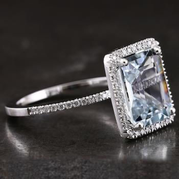 halo ring with a central emerald cut aquamarin surrounded with castle set smaller brilliant cut diamonds