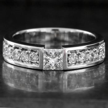 slim solitaire ring with a princess cut diamond under which a small join and next to that smaller pavé set diamonds finished with an engraving