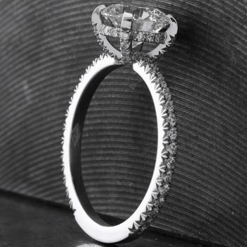 Ring with a larger brilliant cut diamond set with four set studs on a band with a rectangular profile castle fishtail pavé set with small brilliant cut diamonds