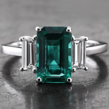 ring with an emerald cut Zambian emerald with oil treatment next to which two baguette cut diamonds along the length set with prongs
