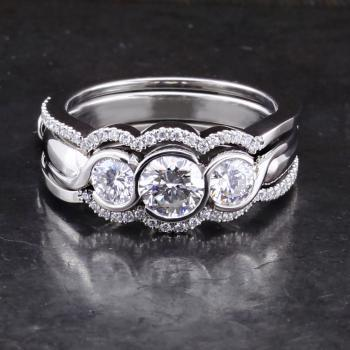trilogy ring with brilliant cut diamonds set in round bezel settings mounted between two fixed matching castle set bands