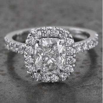 entourage or halo set ring with a central cushion cut diamond surrounded by on the band with slightly curved palmettes and castle set with smaller brilliants (V mounted slightly higher for a close matching wedding band)