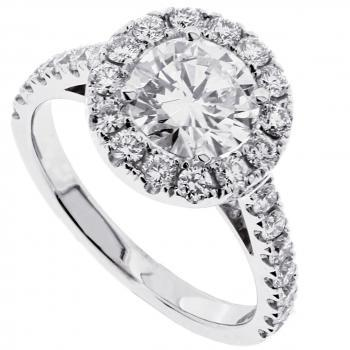 halo ring with a larger central brilliant cut diamond surrounded by smaller bond with palmettes