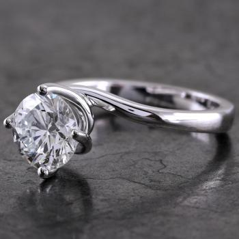 handmade solitaire ring with a brilliant cut diamond in a twisted setting with four claws lozange on the slightly rounded band that extends like a prong on the furthest side of the same side