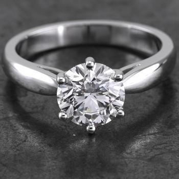 solitaire or engagement ring with a brilliant cut diamond set with six prongs finished with rounded claws mounted between a band with low downward bent arches narrowing like a drop to the diamond