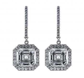 halo earrings with two central assher cut diamonds surrounded with smaller brilliant cut diamonds pending on a clip system
