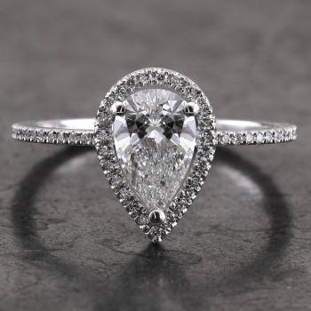 halo ring with a central pear cut diamond surrounded with castle set smaller brilliant cut diamonds
