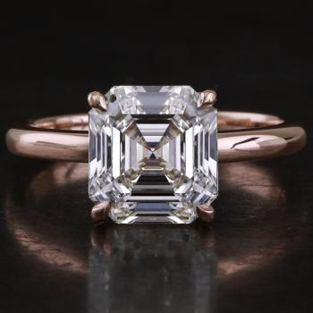solitaire ring with an emerald cut diamond set with four single prongs on a fine band with a D-shaped profile
