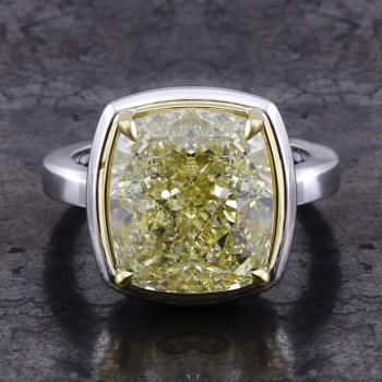 solitaire ring with a central cushion cut light fancy yellow diamond set with claws above a thin yellow basket surrounded with a fine white border