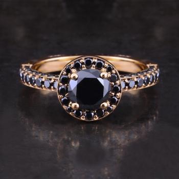 halo ring with a central brilliant-cut black diamond surrounded by smaller black diamonds pavé set with an engraved border